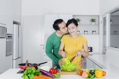 Husband kisses his wife in kitchen Stock Photography