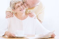 Husband kissing elderly woman`s cheek. Happy elderly women reading newspaper and her husband kissing her cheek Royalty Free Stock Photo