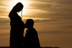 Husband kissing his pregnant wife, silhouette couple at sunset Stock Photography