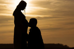 Husband kissing a pregnant wife, silhouette couple at sunset.  royalty free stock photos