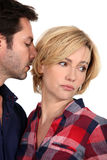 Husband kissing unhappy wife Royalty Free Stock Image