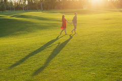 Husband  leading the hand of his wife on green field Royalty Free Stock Photos
