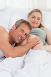Husband listening to his wife's belly Stock Image