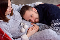 Husband listening to his wife's belly at home Stock Images
