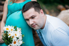 Husband listening to his wife's belly outdoor Royalty Free Stock Photos