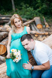 Husband listening to his wife's belly outdoor Stock Photography