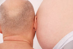 Husband listens to the stomach of pregnant wife Royalty Free Stock Photos