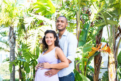 Husband looking away while touching pregnant wife belly Stock Images
