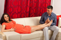 Husband massage pregnant wife. Husband massaging his pregnant wife legs and sitting together on couch in their home royalty free stock images