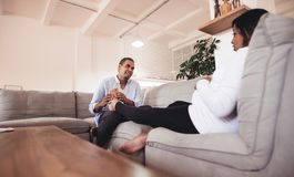 Husband massaging his pregnant wife legs. While sitting together on sofa. Man giving feet massage to pregnant women at home royalty free stock images