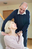 Husband massaging neck to wife Stock Image