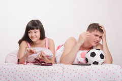 Husband not upset by a goal scored, skeptical wife smiling Royalty Free Stock Photography
