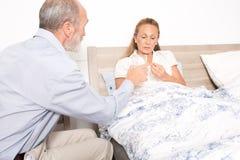 Husband nursing his wife Stock Image