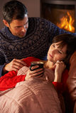 Husband Nursing Sick Wife With Cold. Resting On Sofa By Cosy Log Fire Royalty Free Stock Photos