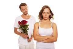 Husband offering roses to unhappy wife Royalty Free Stock Image