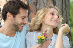 Husband offering wife flowers. To his wife Stock Photos
