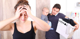 Husband overwhelmed by taking care of everything alone, because his wife is suffering from postpartum depression Royalty Free Stock Photos