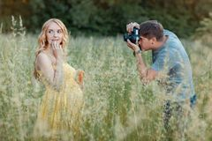Husband photographs the pregnant wife in a field Royalty Free Stock Photography