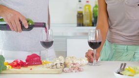 Husband pouring red wine in kitchen Royalty Free Stock Photography