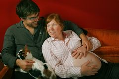 Husband and pregnant wife. Family time - husband with cat on his knee and hand on pregnant wife's belly stock photos