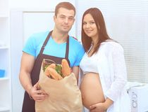 Husband and pregnant wife holding a package of baguettes royalty free stock images