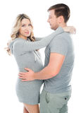Husband and pregnant wife hugging each other. Andp fondle abdomen royalty free stock images