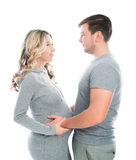 Husband and pregnant wife hugging each other. And fondle abdomen royalty free stock photography