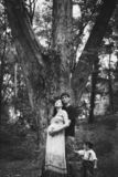 A husband, a pregnant wife and a little son are standing near a big tree, the child is holding a dad by his pants. Husband hugs pregnant wife from back stock photo