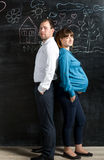 Husband and pregnant wife posing against black wall with drawing Royalty Free Stock Photography