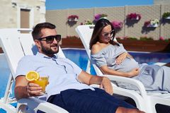 Husband and pregnant wife relaxing on lounge near pool stock photos