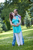 Husband with pregnant wife is resting in nature. Royalty Free Stock Images