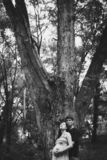 Husband and pregnant wife are standing near a big tree, her eyes are closed, the husband is hugging the pregnant wife. From the back. Les. Black and white photo royalty free stock image