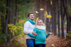Husband and pregnant wife are walking in autumn park.  royalty free stock photography