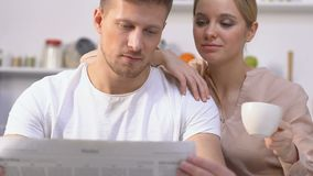 Husband reading morning newspaper, wife drinking coffee admiring life, family. Stock footage stock video footage