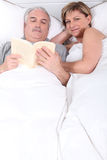 Husband reading next to his wife Royalty Free Stock Images