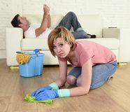 Husband resting on couch while wife cleaning doing housework in chauvinism concept Stock Image