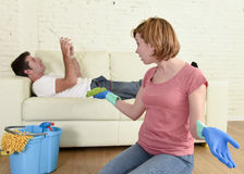 Husband resting on couch while wife cleaning doing housework in chauvinism concept Royalty Free Stock Photo