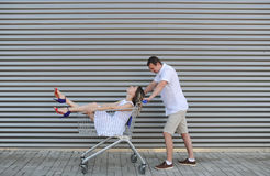 The husband rolls the wife in the cart for foodstuff. Royalty Free Stock Photo