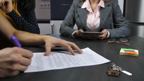Husband`s hands signing mortgage contract