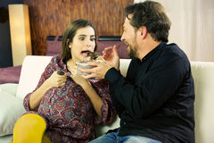 Husband satisfies the cravings of pregnant young woman giving her  ice-cream Royalty Free Stock Photos