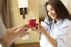Husband serves coffee in bed to his wife and awaking her Royalty Free Stock Images
