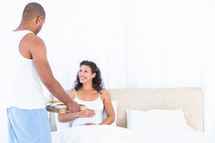 Husband serving breakfast for happy pregnant wife. On bed at home Stock Image