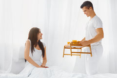 Husband serving wife breakfast in bed. Young handsome husband serving his beautiful happy wife breakfast in bed . Love and care. Relationships concepts Royalty Free Stock Images