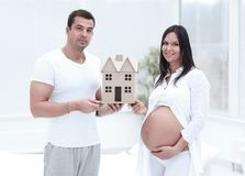 Husband showing his pregnant wife a layout of their future home. stock photo
