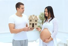 Husband showing his pregnant wife a layout of their future home. Concept of perspective Stock Image