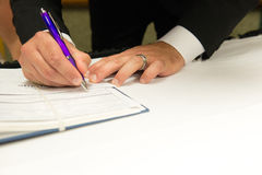 Husband signing Marriage Document. Male with Purple Pen signing Marriage Documents on white linen table providing lots of space for advertising copy Stock Image
