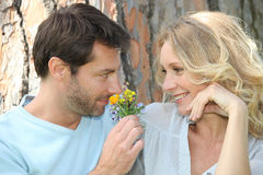 Husband smelling flower Stock Images