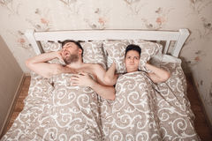 Husband snores in a dream, wife closes ears. Royalty Free Stock Photo