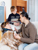 Husband and son caring for sick woman Stock Photos