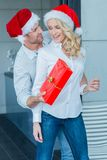Husband surprising his wife with a Christmas gift Royalty Free Stock Images
